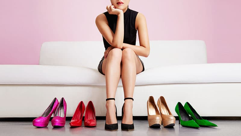 Woman thinking on the sofa with many shoes.Beautiful colorful hi